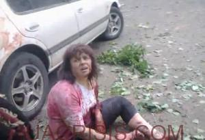 Woman, after Ukrainian army bombing asks cameraman to help people across the street.